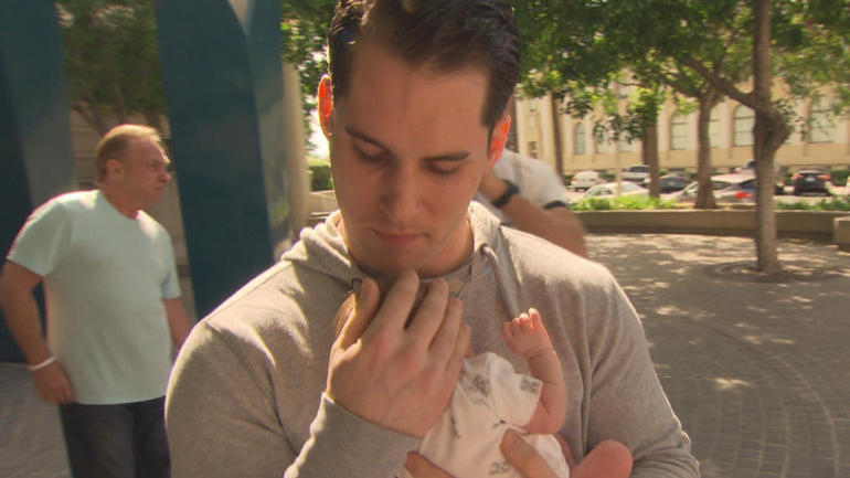 Christian Smith holds his newborn daughter for the first time